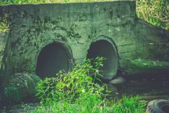 Old Drain Pipe Retro. Large old concrete drain pipe, culvert in the grass, filtered background Royalty Free Stock Images