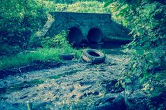 Old Drain Pipe Retro. Large old concrete drain pipe, culvert in the grass, filtered background Royalty Free Stock Photos