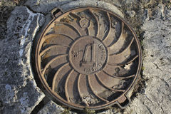 Old drainage, cast iron manhole, Soviet-made. Cover the drain hatch iron material, is produced in the Soviet Union stock photos