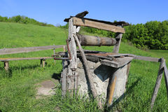 Old draw well on green meadow Royalty Free Stock Photography