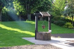 Old Draw well. Old wooden and stone,water well in the nature, between the trees. With a wood bucket and chain Royalty Free Stock Photography
