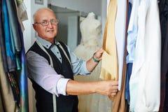 Old Dress-Maker Showing garments in Studio Stock Photo