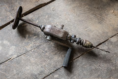 Old drill in the warkshop. Old hand operated drill on the dusty workshop, wooden table Stock Image