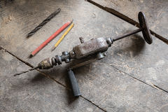 Old drill in the warkshop. Old tools on the dusty workshop, wooden table, pencils and drill Stock Images