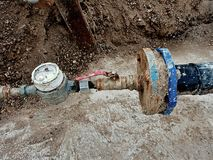 Old drink waser pipe, hydrometer and  shut-off valve on  plastic tube. Repairing of drink water system. Stock Photo