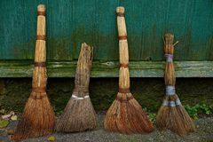 A set of old brooms stand at the green wooden wall Stock Photo