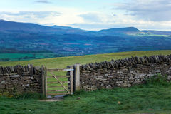 Old dry stone wall in welsh countryside, mountains in background Royalty Free Stock Image