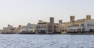 Old Dubai wind towers along the Dubai creek, as seen from an Abra water taxi. On a clear summers morning stock photography