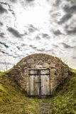 Old dug-out building. Under a cloudy sky stock photo
