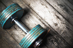 The old dumbbell on the wooden floor. Royalty Free Stock Images