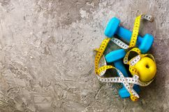 Turquoise dumbbells with measuring tape and yellow apple on concrete background. Free space for your text. Sport concept. Old dumbbells with measuring tape and Stock Photography