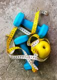 Turquoise dumbbells with measuring tape and yellow apple on concrete background. Free space for your text. Sport concept. Old dumbbells with measuring tape and Stock Photo