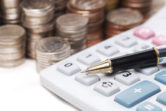 Old dusty ball pen on calculator with stack coins background. Old dusty ball pen on calculator Royalty Free Stock Photo