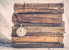 Old dusty books. Pile of old dusty books with broken pocket watch on dirty white Stock Photos