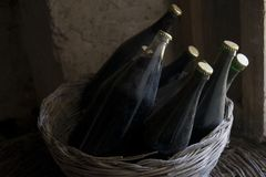 Old red wine bottles in a wicker basket Stock Photos