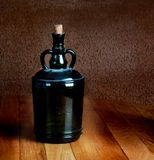Old dusty bottle on a wooden table Royalty Free Stock Image
