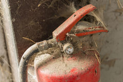 Old dusty fire extinguisher. In a barn stock photography