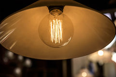 Old dusty light bulb. Glowing in the dark Stock Image