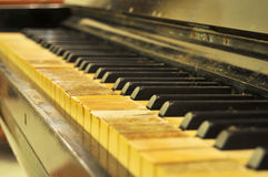 Old Dusty Piano. A shot of an old piano with stained ivory keys with missing ivory pieces missing that was not maintained very well Stock Image