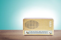 Old dusty radio from 1970 on wooden table with mint green backgr Royalty Free Stock Photo