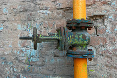 Old dusty and rusty valve and pipes of yellow color on weathered brick wall Stock Photo
