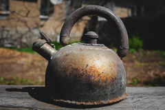 Old dusty teapot. Outdoors in wooden table Stock Photo