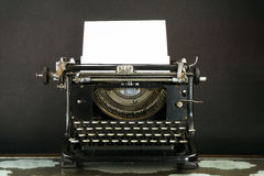 Old and Dusty Typewriter with a sheet of paper. Old, Dusty Typewriter on dark background royalty free stock image