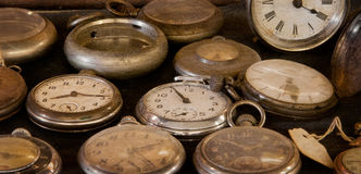 Old Dusty Watches. Vintage pocket watches gather dust in display case - texture added for vintage feel stock photos