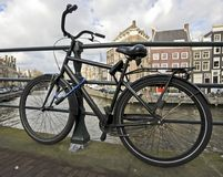 Old dutch bike  chained against a bridge. Old dutch bike against a bridge in Amsterdam Netherlands Royalty Free Stock Photos
