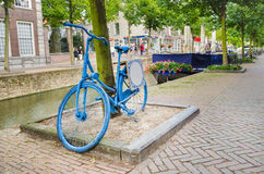 Old Dutch blue bicycle. Parked by a canal in Delft Stock Image
