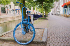 Old Dutch blue bicycle. Parked by a canal in Delft Stock Photography