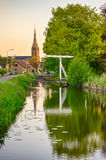 Old Dutch bridge, canal and church. Old Dutch bridge under the big tree, canal and church in the village of Nootdorp, hdr image, focus on bridge and church Royalty Free Stock Image