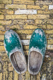 Old Dutch clogs on a brick background Stock Photo