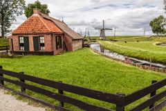 Old Dutch Cottage & Windmill royalty free stock photography