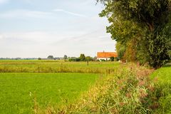 Old Dutch farmhouse with an orange tiled roof. Old white plasterd Dutch farmhouse in North Brabant with an orange tiled roof as seen from the edge of the stock photo