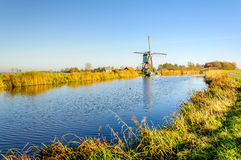 Old Dutch windmill at the bank of a canal. Picturesque and colorful polder landscape in the Netherlands with an historic windmill next to water on a sunny day in Stock Photo