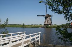 Old Dutch windmill in Holland. Beautifull scene of a pier, water and a historical windmill Stock Image