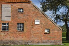 Old East Frisian farmhouse part. Partial view on the weathered gable wall of an old East Frisian farmhouse with a dithering tree Royalty Free Stock Image