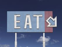 Old Eat Arrow Sign. Retro eat arrow sign with blue sky near historic route 66 Stock Images