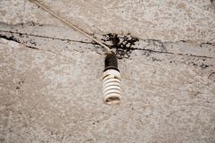 Old economical light bulb hanging on the old concrete ceiling. White wires royalty free stock photo