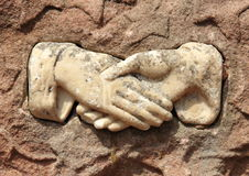 Old effigy of shaking hands in marble Royalty Free Stock Image