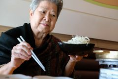 Old elderly elder woman eating food in restaurant. senior lifestyle. Concept royalty free stock photo