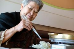 Old elderly elder woman eating food in restaurant. senior lifestyle. Concept royalty free stock photos