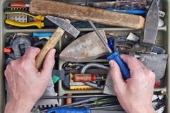 The old  elderly repairman  examines rusty tools in his dirty ru Royalty Free Stock Image