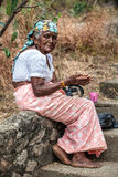 Old elderly woman begging. Sri Lanka. An Elderly woman with hands asking for charity is sitting on a low wall on the street. She wears clothes of Asian culture Royalty Free Stock Photo