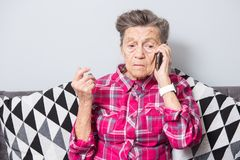An old elderly woman grandmother with gray hair sits at home on the couch using the hand phone, a telephone conversation royalty free stock images