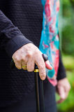 Old elderly woman with scarf walking with stick. Old elderly woman with scarf holding a walking stick closeup Stock Photo