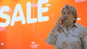 Old elderly woman talks using smart phone indoors stock video