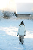 Old elderly woman in warm clothes walking home through heavy snow on a cold winter morning at sunrise Stock Photos