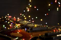Old electric guitar with a lighted garland on a dark background. Greeting, Christmas, New Year greeting card. Copy space. Old electric guitar with a lighted Stock Images
